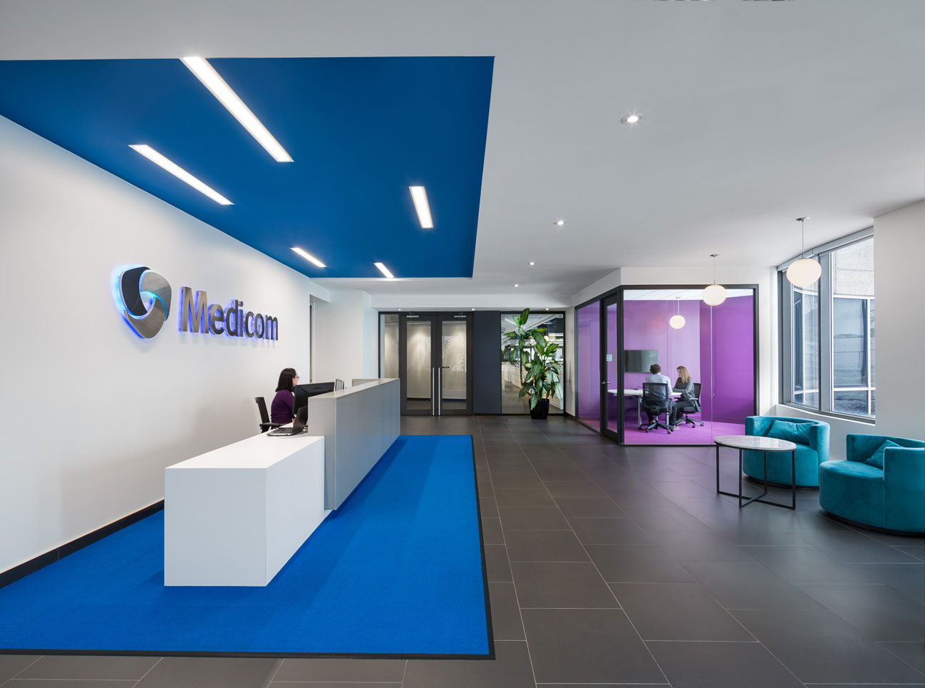 White reception desk on blue carpet with blue recessed ceiling, Medicom logo on wall and glass cube meeting area  finished in purple.
