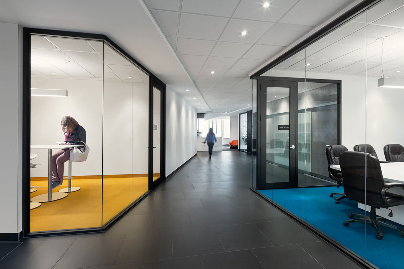 Corridor with glass cube meeting rooms on left and right, left with turquoise carpet, right with yellow wall and carpet.