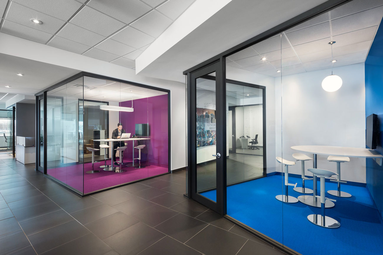 View of Medicom offices showing 2 glass box meeting rooms, one blue and one purple with an employee working on a laptop..