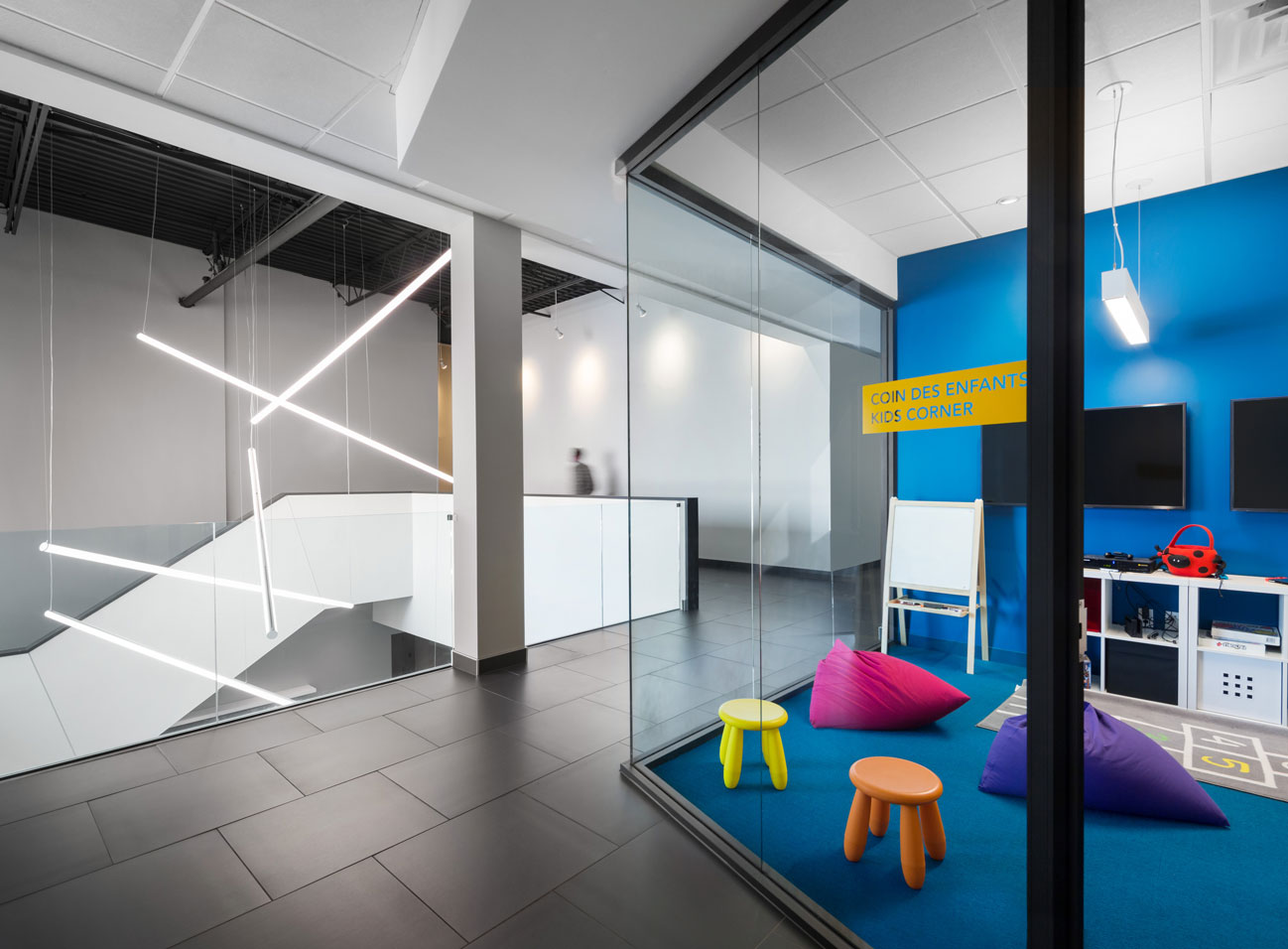 In-office daycare at Medicom showing blue wall and carpet and bright colored stools and bean bag chairs, staircase and suspended lights in background.