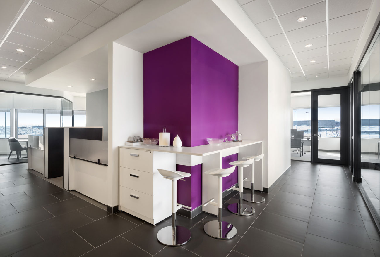 Coffee bar at Medicom offices with white chairs and cabinets and purple accent wall.
