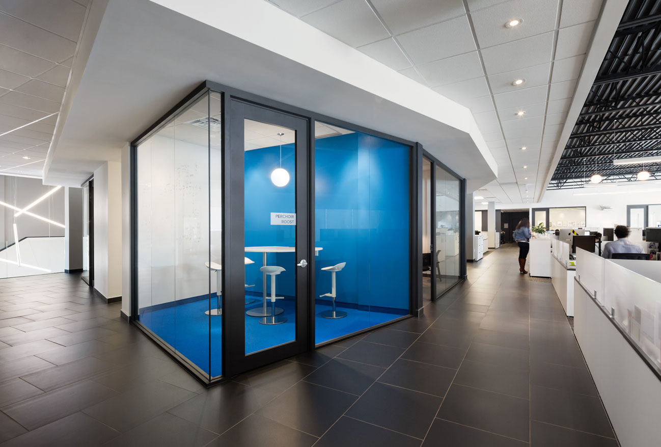 Glass cube meeting room with blue wall and floor with view of open corridor and person walking.