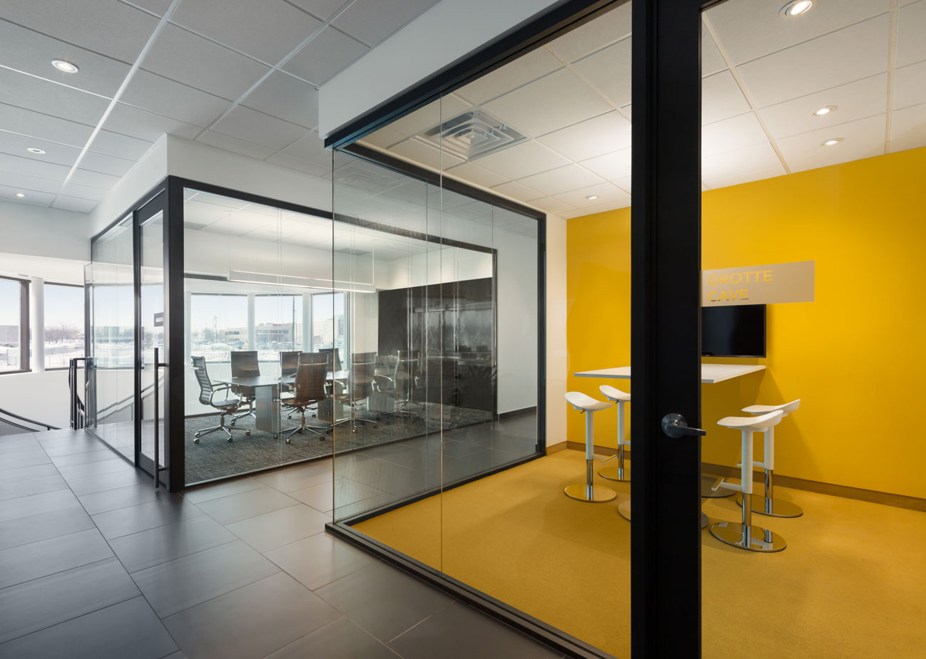 Glass cube meeting room with yellow floor and wall and formal neutral colored meeting room in background.